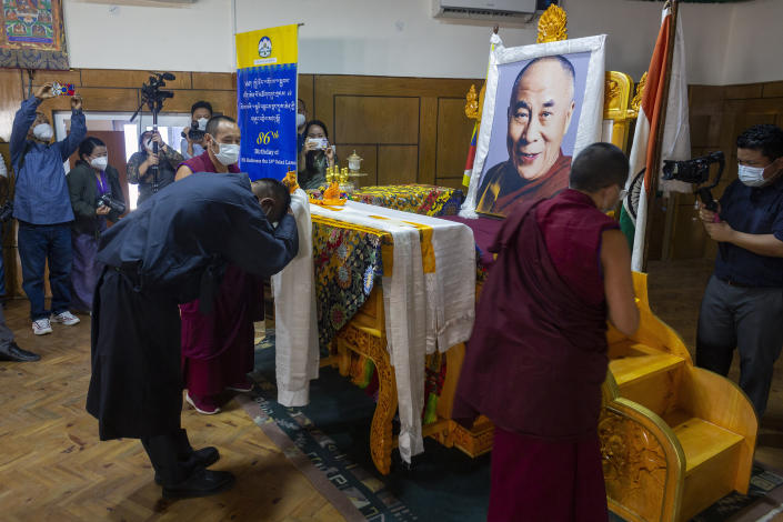 President of the Central Tibetan Administration Penpa Tsering, offers a ceremonial scarf in front of a portrait of his spiritual leader the Dalai Lama during a ceremony to mark the 86th birthday of the Tibetan leader in Dharmsala, India, Tuesday, July 6, 2021. This year, due to the coronavirus pandemic, the celebrations were muted and behind closed doors. (AP Photo/Ashwini Bhatia)