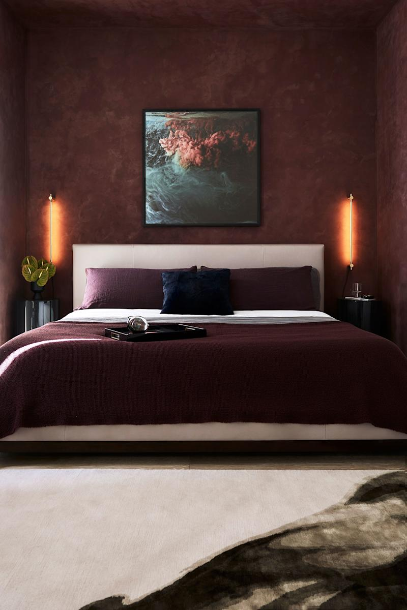 Both the designer, who studied at NYU's Tisch School of the Arts, and the homeowners are cinephiles. The movie Scarface was an inspiration for the moody atmosphere of the master bedroom, with deep burgundy walls covered in Ressource Peintures' limewash paint in Chianti. Thin brass sconces from Juniper, which provide a halo effect, and a large-scale photograph by Christian Stoll showing dark billowy clouds add to the midnight vibe.