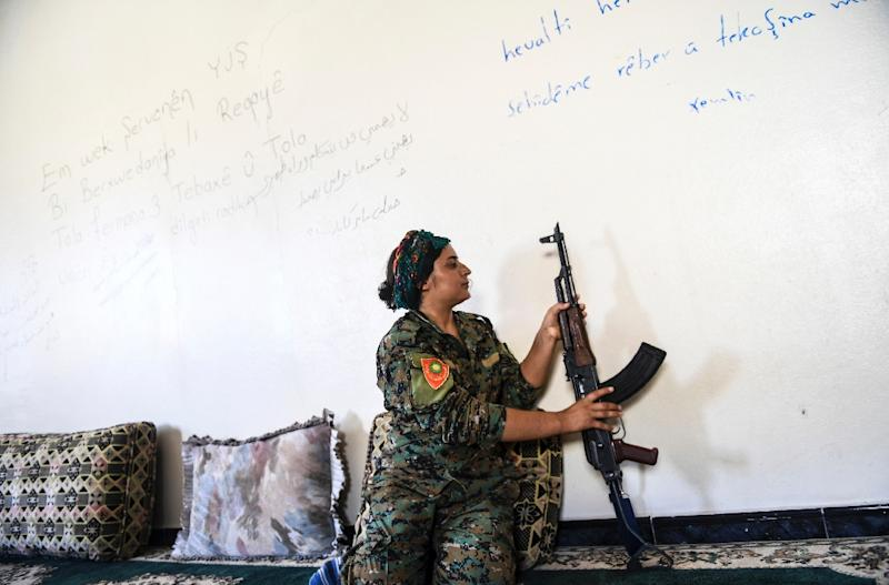Yazidi fighter Heza prepares her rifle in an abandoned home used as a base on the eastern outskirts of Raqa on July 18, 2017 (AFP Photo/BULENT KILIC)