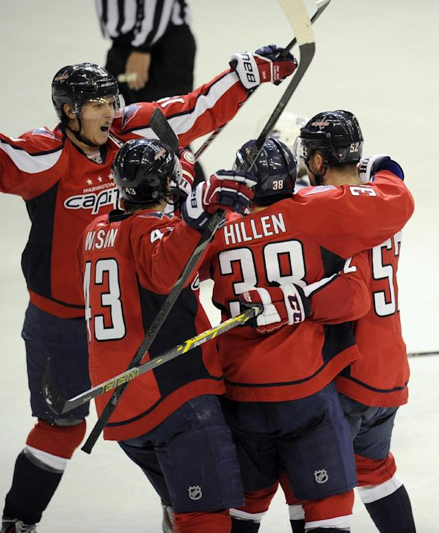 Washington Capitals defenseman Mike Green (52) celebrates his goal with Jack Hillen (38), Tom Wilson (43) and Nicklas Backstrom, left, during the third period of an NHL hockey game against the Vancouver Canucks, Friday, March 14, 2014, in Washington. The Capitals won 4-3. (AP Photo/Nick Wass)