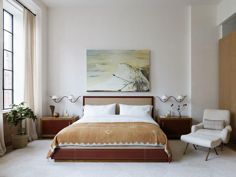 Laura's quietly luxurious master bedroom has a custom bed and bedside tables by Laura Santos Interiors fabricated by Dune. The iconic wall sconces are from 1950 by French designer Jean Royère, circa 1950 from H.M. Luther. The sculptural Italian 1950s chair and ottoman are by Marco Zanuso from the Wooster Gallery. The throw at the end of the bed is a vintage Moroccan silk kilim that Santos collected on her travels. The rug was sourced from FJ Hakimian. The custom drapes are made from fabric by de Le Cuona. The painting is by Dana Schutz.