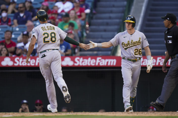 Oakland Athletics' Matt Olson, left, is congratulated by Matt Chapman after he scored on a sacrifice fly by Jed Lowrie during the 10th inning of a baseball game against the Los Angeles Angels, Sunday, Sept. 19, 2021, in Anaheim, Calif. (AP Photo/Jae C. Hong)