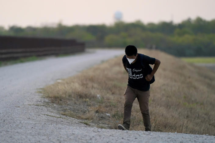 """A migrant walks on a levy after he was caught trying to cross the U.S.-Mexico border, Sunday, March 21, 2021, in Abram-Perezville, Texas. The fate of thousands of migrant families who have recently arrived at the Mexico border is being decided by a mysterious new system under President Joe Biden. U.S. authorities are releasing migrants with """"acute vulnerabilities"""" and allowing them to pursue asylum. But it's not clear why some are considered vulnerable and not others. (AP Photo/Julio Cortez)"""