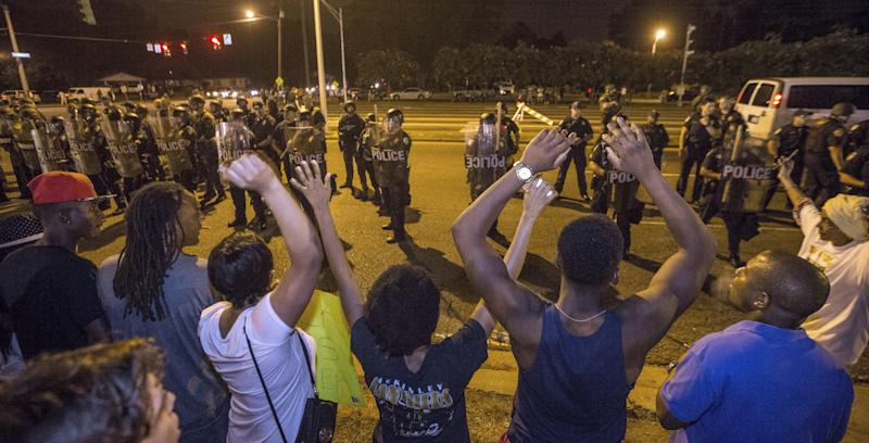 BATON ROUGE, LA -JULY 10: Protesters shout 'Hands up, don't shoot' as law enforcement gather before charging the protesters to make arrests on July 10, 2016 in Baton Rouge, Louisiana. Alton Sterling was shot by a police officer in front of the Triple S Food Mart in Baton Rouge on July 5th, leading the Department of Justice to open a civil rights investigation. (Photo by Mark Wallheiser/Getty Images)