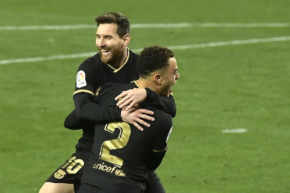 Barcelona's Sergino Dest celebrates with Barcelona's Lionel Messi scoring his side's 3rd goal during the Spanish La Liga soccer match between Real Sociedad and FC Barcelona at Reale Arena stadium in San Sebastian, Spain, Sunday, March. 21, 2021. (AP Photo/Alvaro Barrientos)