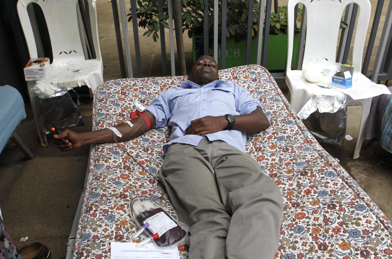 A man donates blood at a temporary donation centre for injured victims of a crossfire between armed men and the police at the Westgate shopping mall, in Kenya's capital Nairobi September 22, 2013. Islamist militants were holed up with hostages on Sunday at a shopping mall in Nairobi, where at least 59 people have been killed in an attack by the al Shabaab group that opposes Kenya's participation in a peacekeeping mission in neighboring Somalia. REUTERS/Thomas Mukoya (KENYA - Tags: CIVIL UNREST CRIME LAW)