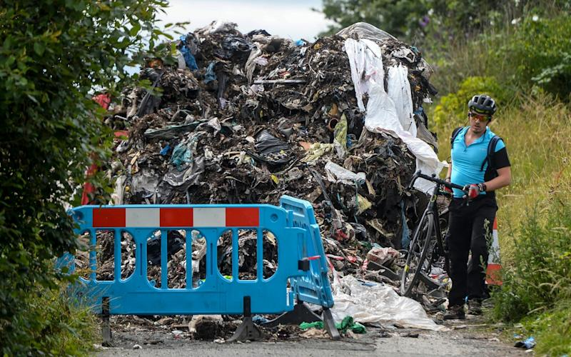A cyclists tries to get past the rubbish that was dumped in Stockport on Friday  - Dan Rowlands / SWNS