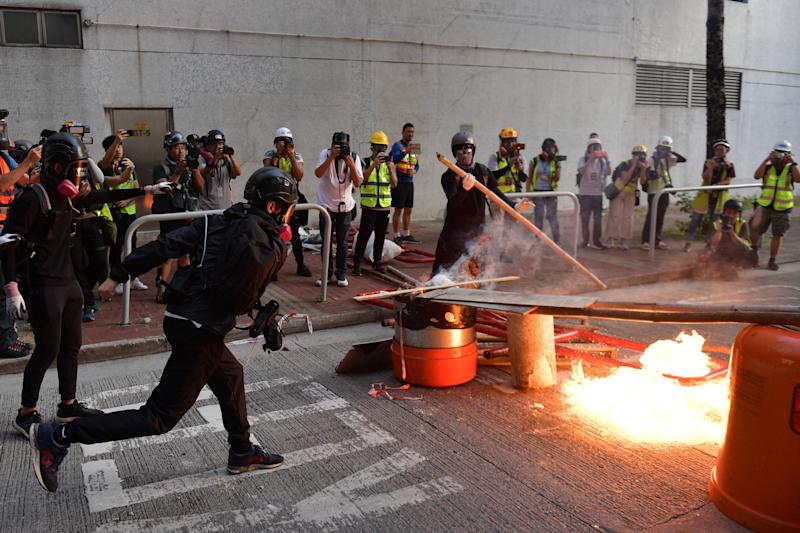 A pro-democracy protester throws a molotov cocktail to set a barricade on fire during clashes with police (AFP/Getty Images)