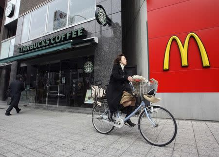 A cyclist rides past branches of Starbucks and McDonald's in the Jimbocho district of Tokyo, in this file picture taken  March 15, 2007.   REUTERS/Kevin Coombs/Files