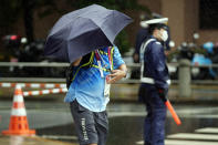 An Olympic worker holds an umbrella against strong wind and rain prior to the women's triathlon competition at the 2020 Summer Olympics Tuesday, July 27, 2021, in Tokyo, Japan. (AP Photo/Eugene Hoshiko)