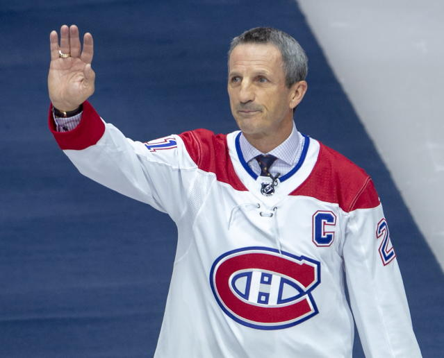 Former Montreal Canadien Guy Carbonneau waves to fans as he gets a standing ovation for his induction into the Hockey Hall of Fame during pre-game ceremonies in Montreal, Wednesday, Nov. 20, 2019. (Ryan Remiorz/The Canadian Press via AP)