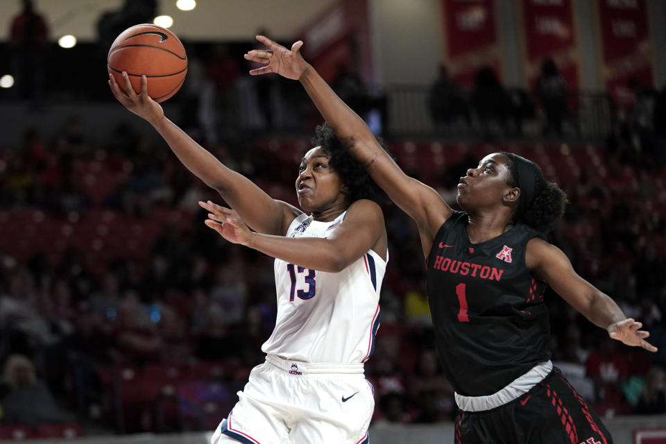Connecticut's Christyn Williams (13) goes up for a shot as Houston's Bria Patterson (1) defends during the second half of an NCAA college basketball game Saturday, Feb. 29, 2020, in Houston. Connecticut won 92-40. (AP Photo/David J. Phillip)