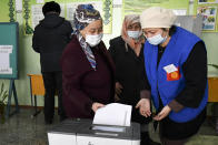 An elderly woman, wearing a face mask to protect herself against coronavirus, casts her ballot during the presidential elections in Gornaya Maevka village, about 25 kilometers (16 miles) south-west of Bishkek, Kyrgyzstan, Sunday, Jan. 10, 2021. Voters in Kyrgyzstan are casting ballots in an early presidential election that follows the ouster of the nation's previous president. President Sooronbai Jeenbekov was forced to step down on Oct. 15 under pressure from demonstrators who challenged the results of a parliamentary vote earlier that month. (AP Photo/Vladimir Voronin)