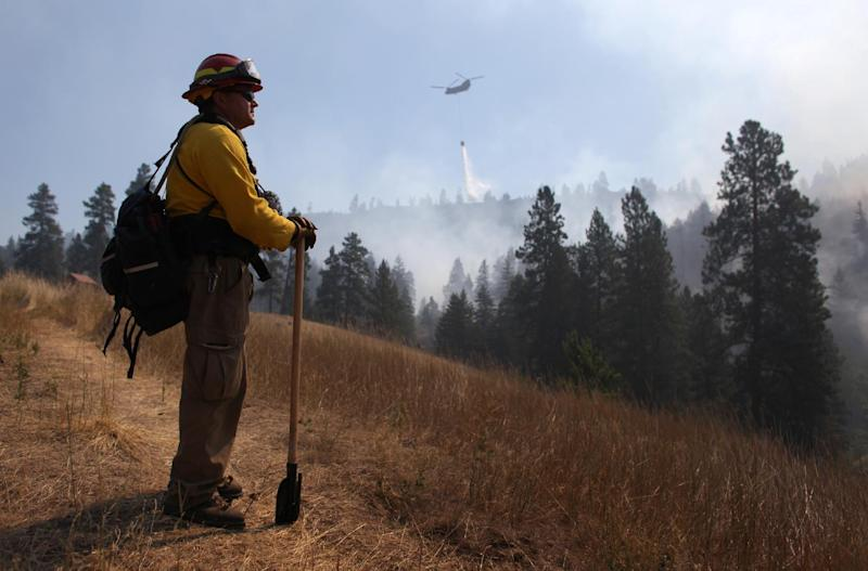 Tracy Summers of Toledo, Wash. monitors the scene above Hidden Valley Ranch where fire crews worked to halt progression of the Taylor Bridge Fire on Thursday, August 16, 2012 near Cle Elum, Wash.. The Taylor Bridge Fire has forced hundreds to evacuate and has burned dozens of homes near Cle Elum, Wash. (AP Photo/seattlepi.com, Joshua Trujillo) MAGS OUT; NO SALES; SEATTLE TIMES OUT; MANDATORY CREDIT; TV OUT