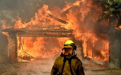 Firefighters battle to save one of many homes burning - Credit: GENE BLEVINS/Reuters