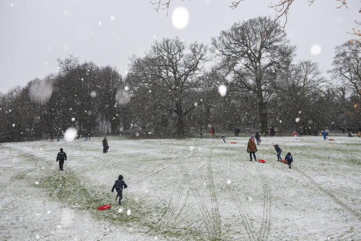 People enjoying the wintry weather at Darley Park, in Derby, central England, Tuesday Dec. 29, 2020.  Snow and ice brought treacherous conditions to many parts of the country overnight, with the cold snap forecast to bite into the new year. (Jacob King/PA via AP)