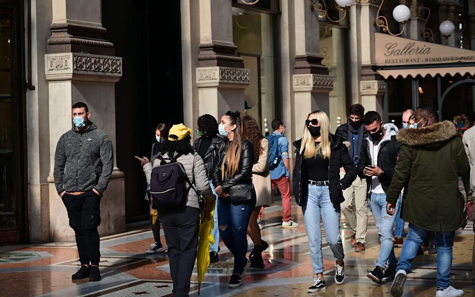 People wearing protective masks walk across the Galleria Vittorio Emanuele II in Milan on October 17, 2020, amid the Covid-19 pandemic - Miguel Medina/AFP