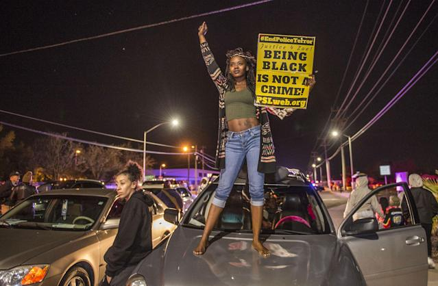 <p>Kianshay Brown of Sacramento stands on a car on Meadoview Rd. as she joined participants of a candlelight vigil in honor of Stephon Clark who marched to the area near where Clark was shot at his grandparents home in Sacramento, Calif., on March 23, 2018. (Photo: Hector Amezcua/Sacramento Bee via ZUMA Wire) </p>