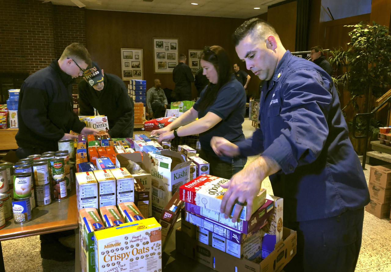 <p> In this Thursday, Jan. 17, 2019 photo, U.S. Coast Guard Culinary Specialist Jerry Wright, right, and Petty Officer 2nd Class Lauren Laughlin, second from right, stack boxes of donated cereal at a pop-up food pantry created at the Coast Guard Academy in New London, Conn. The pantry was created by local Coast Guard-related advocacy groups to help hundreds of civilian and non-civilian Coast Guard employees to help makes ends meet during the partial federal government shutdown. (AP Photo/Susan Haigh) </p>