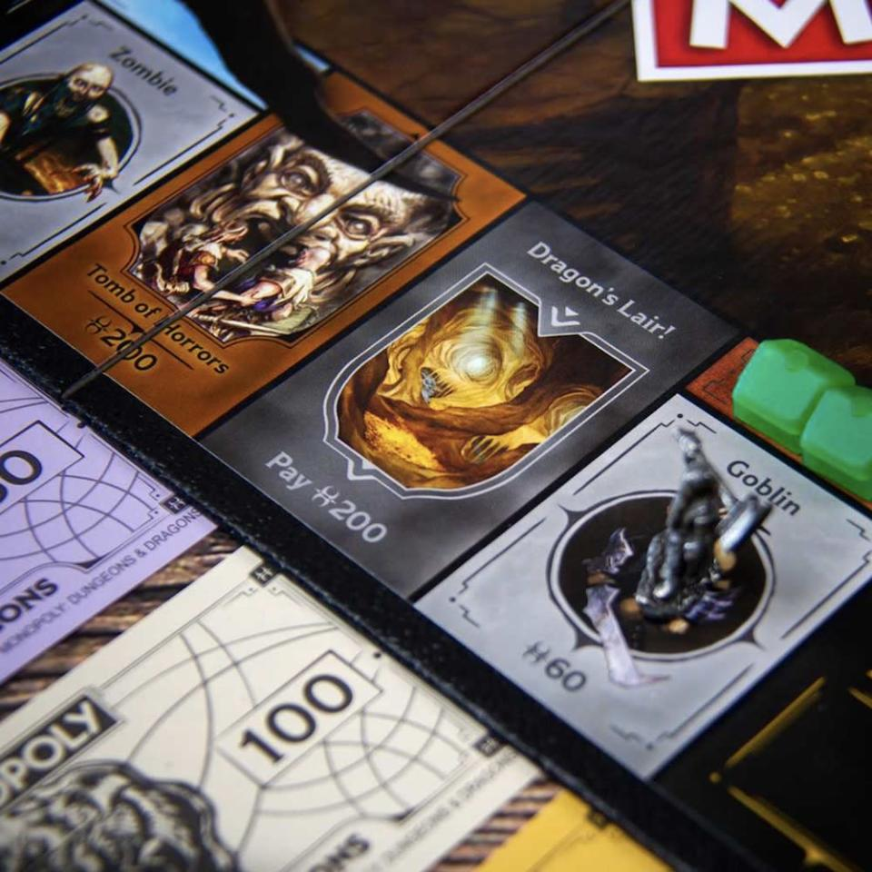 Three board spots from Monopoly: Dungeons & Dragons, with a token on one and fake money underneath