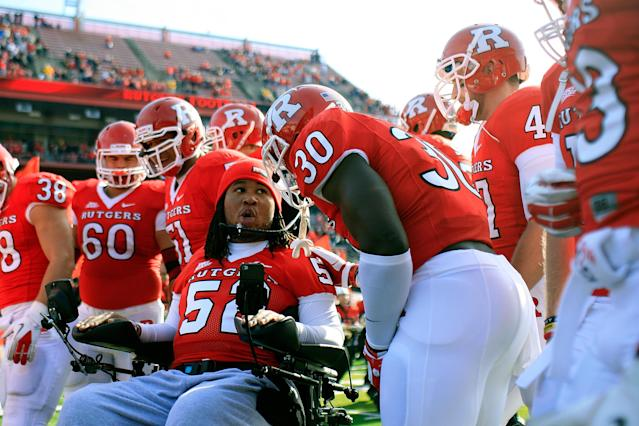 NEW BRUNSWICK, NJ - NOVEMBER 19: Eric LeGrand #52 of the Rutgers Scarlet Knights posses for a photo with teammates on Senior's Day at center field before a game against Cincinnati Bearcats at Rutgers Stadium on November 19, 2011 in New Brunswick, New Jersey. LeGrand was paralyzed during a kickoff return in October 2010. (Photo by Patrick McDermott/Getty Images)