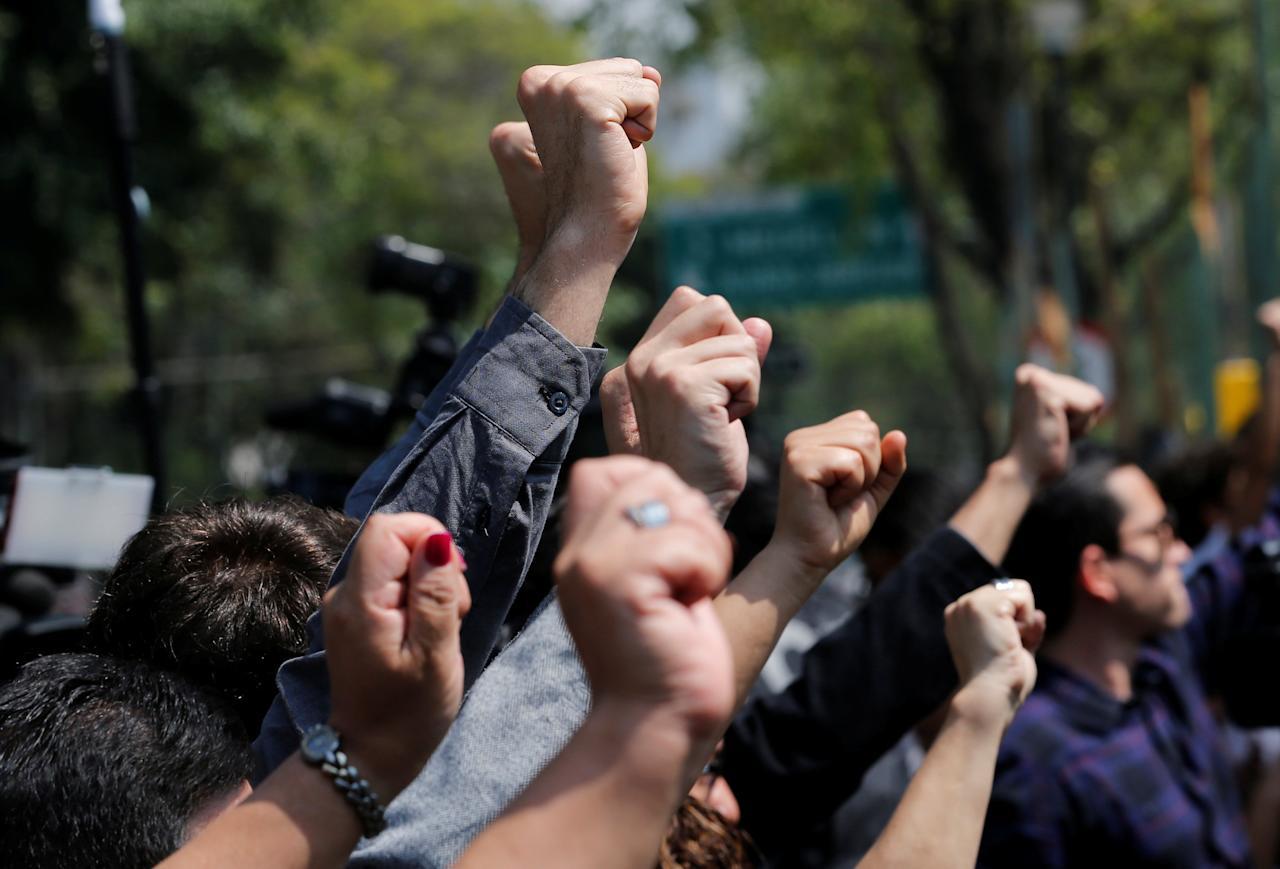 People raise hands outside a collapsed building during a homage in memory of the victims who died in the earthquake on September 19 at Alvaro Obregon Avenue in the Condesa neighbourhood in Mexico City, Mexico, October 19, 2017. REUTERS/Henry Romero