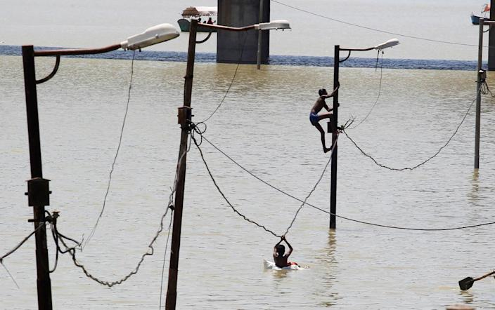 <p>A boy climbs a partially submerged electric pole as he plays with others on the flooded banks of Ganga river, in Allahabad, India, August 21, 2016 (REUTERS/Jitendra Prakash)</p>