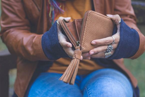 A woman holding open an empty wallet