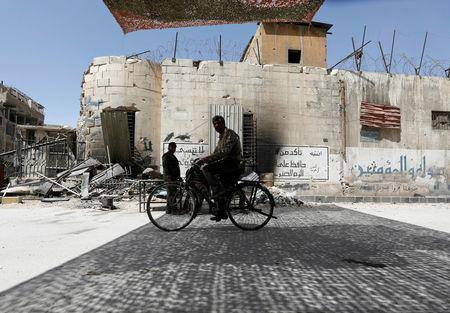 A man rides on a bicycle at the city of Douma in Damascus, Syria, April 20, 2018. REUTERS/Omar Sanadiki