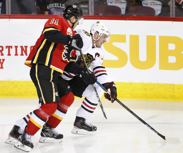Chicago Blackhawks center Jonathan Toews (19) battles Calgary Flames center Mikael Backlund (11) during the second period of an NHL hockey game Saturday, Feb. 15, 2020, in Calgary, Alberta. (Larry MacDougal/The Canadian Press via AP)