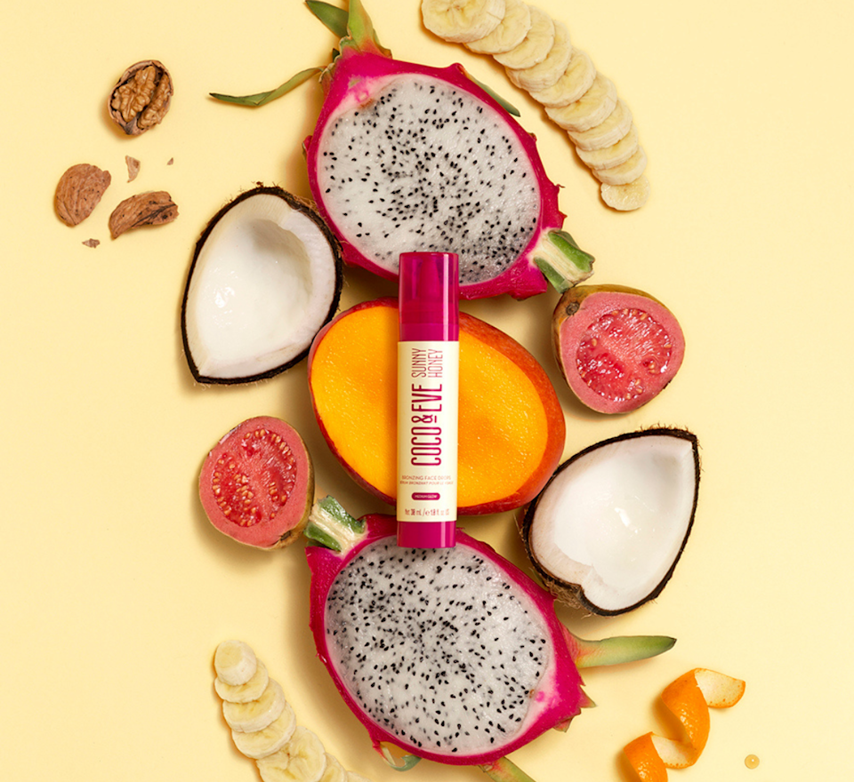 The Coco & Eve Sunny Honey Bronzing Face Drops bottle lying on top of tropical fruits.