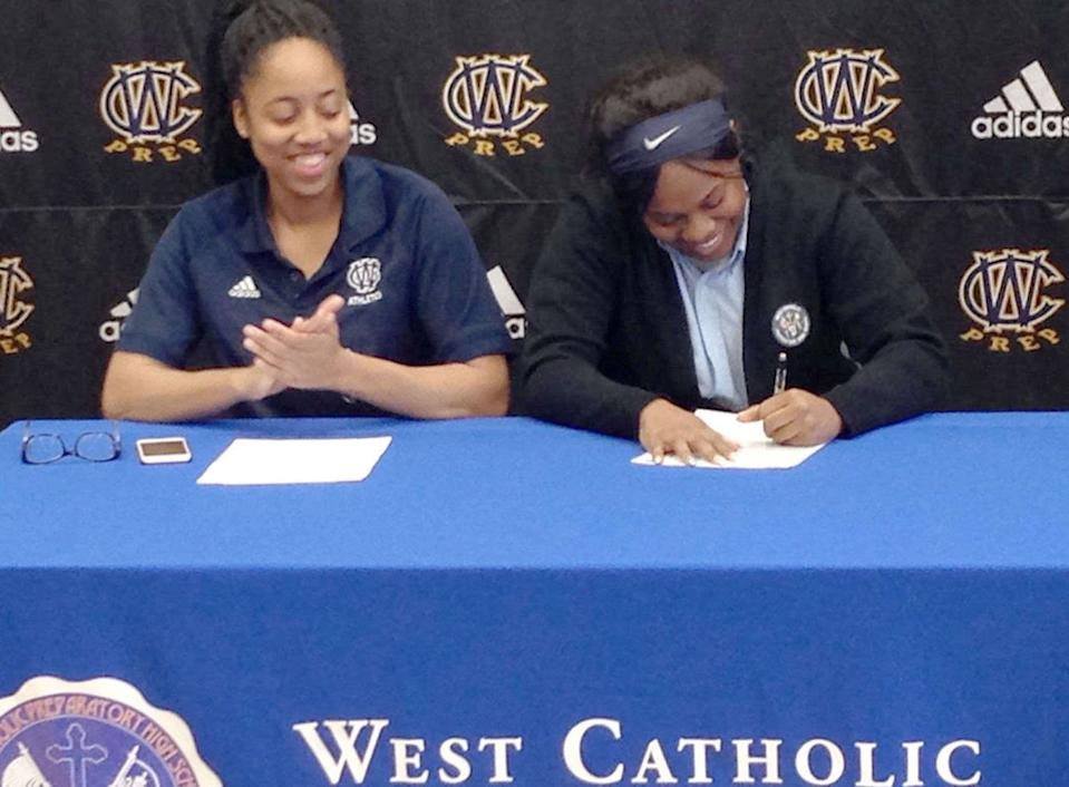 Beulah Osueke watches as Akyra Murray signs a letter of intent to Mercyhurst University in 2016. (Provided by Beulah Osueke)