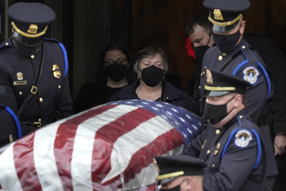 """Janice Evans, center, mother of the late U.S. Capitol Police officer William """"Billy"""" Evans, walks behind a casket holding her son while departing St. Stanislaus Kostka Church following a funeral Mass, in Adams, Mass., Thursday, April 15, 2021. Evans, a member of the U.S. Capitol Police, was killed on Friday, April 2, when a driver slammed his car into a checkpoint he was guarding at the Capitol. (AP Photo/Steven Senne)"""