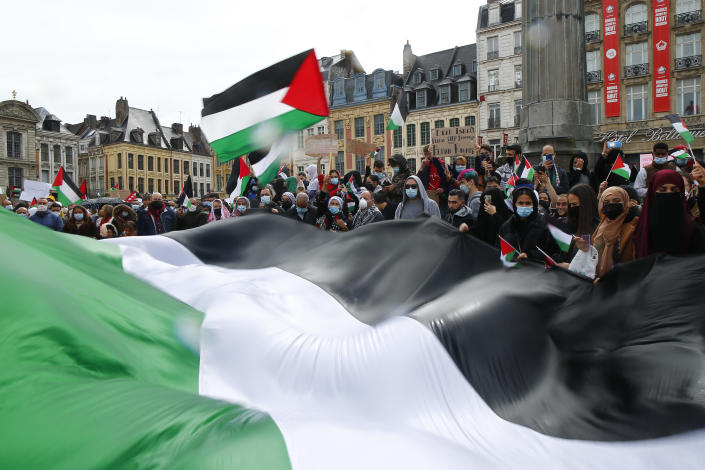 People hold Palestinian flags during a demonstration in Lille, northern France, Saturday May 15, 2021. Marches in support of Palestinians in the Gaza Strip were being held Saturday in a dozen French cities, but the focus was on Paris, where riot police got ready as organizers said they would defy a ban on the protest. (AP Photo/Michel Spingler)