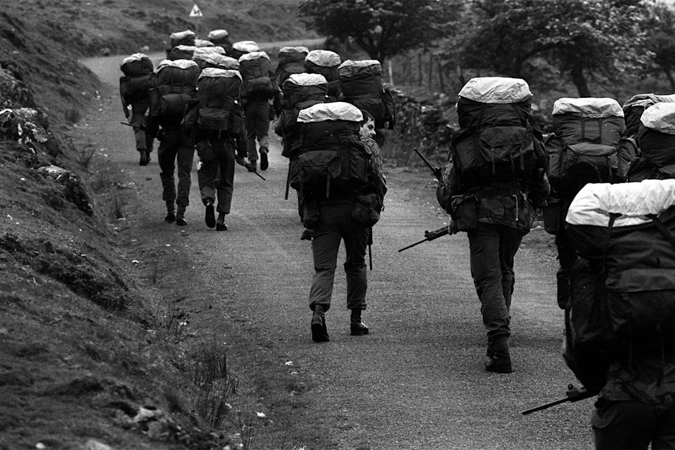 Recruits with 45 lb backpacks and 10 lb FN rifles walk to the top of a mountain before the official start of an endurance march across country because the track is too steep for an Army truck. Allegedly, a recruit who ate a 1lb chocolate bar, making his pack lighter, was made to carry a 2 lb rock instead.