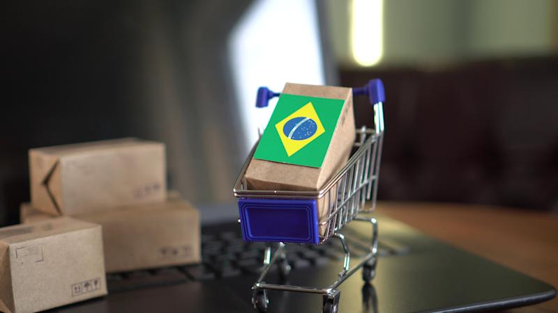 Tiny boxes and cart on computer with Brazilian flag.