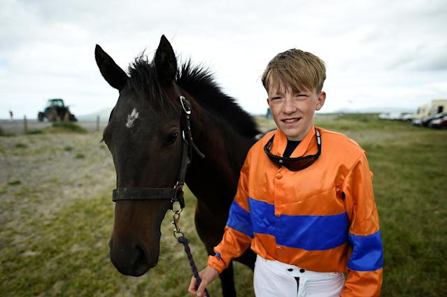 Jockey Eoin Staples aged 14 poses for a photograph before a race meet on the beach in Carrowniskey, Ireland June 25, 2017. REUTERS/Clodagh Kilcoyne