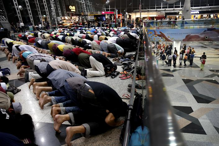 Muslim men offer prayers at the Kuala Lumpur International Airport for the missing Malaysia Airlines jetliner MH370, while on a level down, travellers queue up at immigration checkpoints, Thursday, March 13, 2014 in Sepang, Malaysia. Planes sent Thursday to check the spot where Chinese satellite images showed possible debris from the missing Malaysian jetliner found nothing, Malaysia's civil aviation chief said, deflating the latest lead in the six-day hunt. The hunt for the missing Malaysia Airlines flight 370 has been punctuated by false leads since it disappeared with 239 people aboard about an hour after leaving Kuala Lumpur for Beijing early Saturday. (AP Photo/Wong Maye-E)