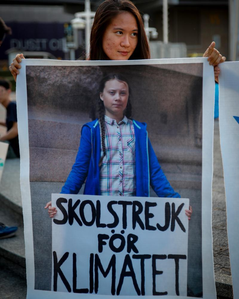 An activist holds a sign with Greta Thunberg's photo during a climate strike