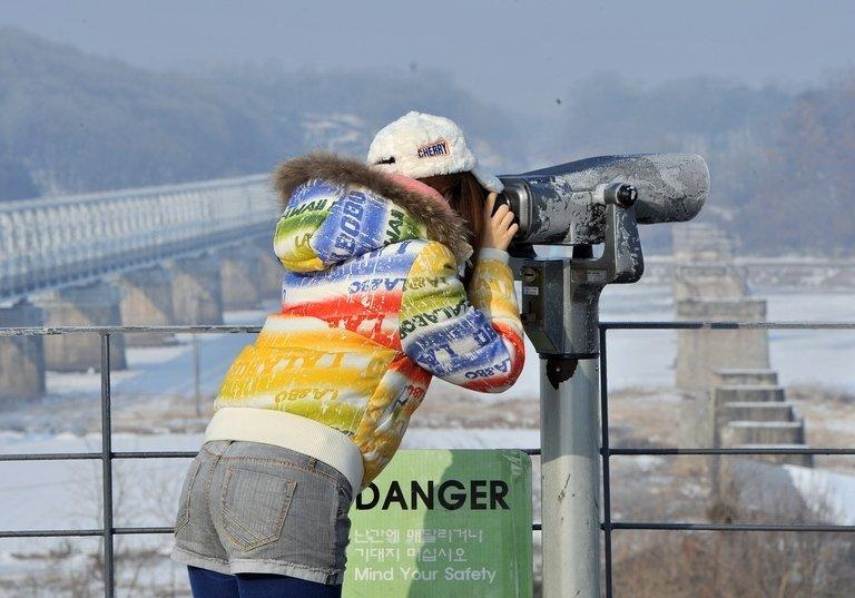 """A visitor looks at North Korea through binoculars at Imjingak in Paju near the demilitarized zone dividing the two Koreas on February 13, 2013. """"The prospect that the North will sell highly-enriched uranium, nuclear weapons designs or even nuclear weapons to all comers, is not a happy thought if you live in one of America's cities,"""" Robert Gallucci, president of the MacArthur Foundation, said"""