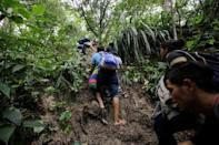 Honduran migrants hike in the forest after crossing the Lempa river, in the border line between Honduras and Guatemala to join a caravan trying to reach the U.S, in Guatemala October 17, 2018. REUTERS/Jorge Cabrera