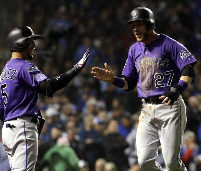 Trevor Story, right, celebrates with Carlos Gonzalez after scoring on a one-run single by Tony Wolters during the 13th inning of the National League wild-card playoff baseball game against the Chicago Cubs. (AP Photo)