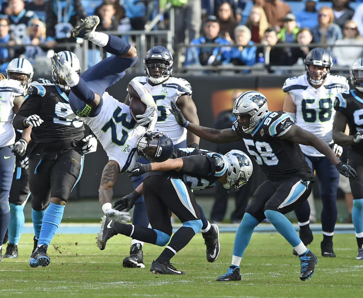 Seattle's Chris Carson (32) is upended by Carolina's Eric Reid (25) in the second half of Sunday's game. Carson surprisingly landed on his feet. (AP)