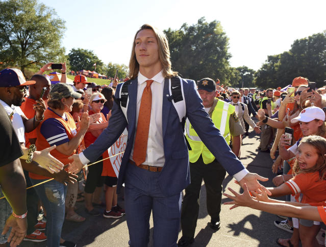 FILE - In this Aug. 29, 2019, file photo, Clemson's Trevor Lawrence greets fans as he arrives for the team's NCAA college football game against Georgia Tech in Clemson, S.C. Lawrence and girlfriend Marissa Mowry have restarted their efforts to raise funds for those affected from the coronavirus in his Georgia hometown and the area of Upstate South Carolina where their colleges are located. (AP Photo/Richard Shiro, File)