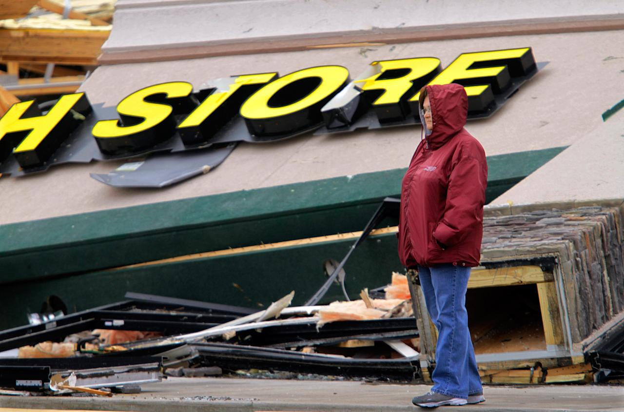 Tammy Jenkins take time from cleaning up to survey the damage to a strip mall Friday, March 2, 2012, in Harrisburg, Ill. A pre-dawn twister flattened entire blocks of homes Wednesday as violent storms ravaged the Midwest and South. (AP Photo/Seth Perlman)