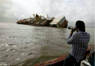 Reuters photographer Danish Siddiqui takes pictures from a fishing boat of the damaged cargo ship MSC Chitra in the Arabian Sea off the Mumbai coast