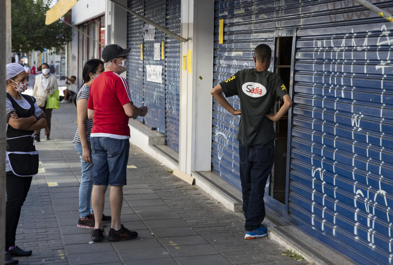 Customers wait to pick-up items bought online outside a store that remains partially open during a state government imposed quarantine to help stem the spread of the new coronavirus in Sao Paulo, Brazil, Monday, June 1, 2020. (AP Photo/Andre Penner)