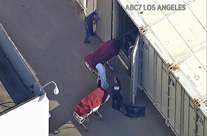 FILE - This file photo from video provided by ABC7 Los Angeles shows workers putting bodies into a refrigerated trailer at the offices of the Los Angeles County Coroner in Los Angeles. More than 500 people are dying each day in California because of the coronavirus. The death toll has prompted state officials to send more refrigerated trailers to local governments to act as makeshift morgues. State officials said Friday they have helped distribute 98 refrigerated trailers to help county coroners store dead bodies. (ABC7 Los Angeles via AP, File)