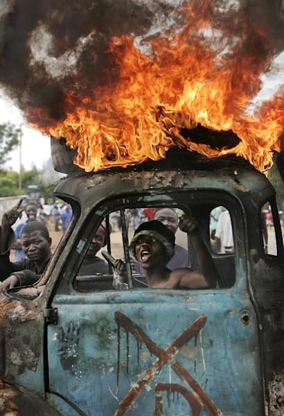 FILE - In this Tuesday, Jan. 29, 2008 file photo, a Kenyan man sits in the cab of a destroyed truck used as a makeshift roadblock while a tyre burns on the roof, as he and others enforce the roadblock, during post-election violence in Kisumu, Kenya. A Kenyan woman said Thursday, Sept. 19, 2013 that she fears for her life after her photo was circulated on social media and on blogs claiming she was the first witness - whose identity was hidden - to testify against Kenya's deputy president during his trial at the International Criminal Court. (AP Photo/Ben Curtis, File)