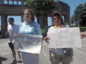 Janine Gerety, left, and Cat Daidone, right, two former Atlantic City N.J. casino workers, hold signs during a demonstration on Atlantic City's Boardwalk on Wednesday, June 30, 2021 in favor of making a ban on smoking in the city's casinos permanent. The pandemic-inspired ban is due to expire on Sunday July 4. (AP Photo/Wayne Parry)